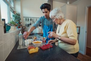 THS worker assists a senior woman to prepare a meal.